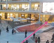 中央の広場を右斜めに、テレビモニターの下から施設内へ